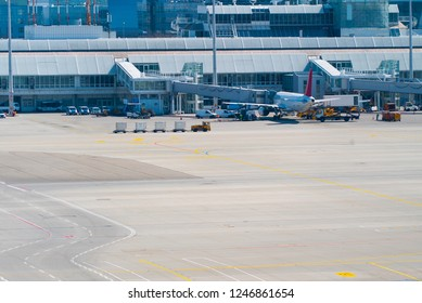 View of airport with small cart and airplane being towed