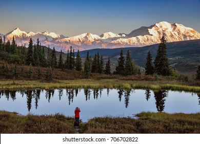 view of alaska's mount denali looms over calm pond at sunset, with clear blue sky above