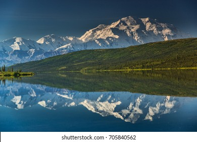 view of alaska's mount denali reflected in calm Wonder Lake, with clear blue sky above