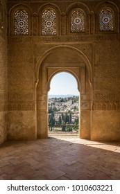 View of the Albayzin district of Granada, Spain, from an arched window in the Alhambra palace near sunset at Granada, Spain, Europe on a bright sunny day