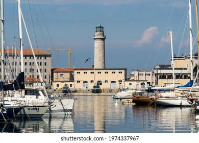 View along the boats of the marina to the Ex Lighthouse La Lanterna in Trieste in Northern Italy