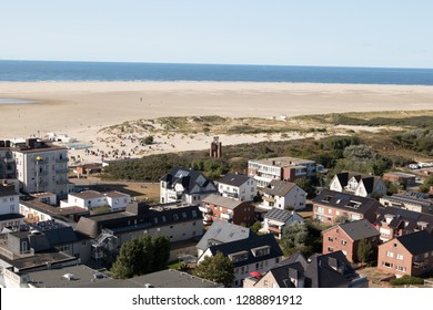 view along the buildings and the beach and the sea at the horizon under a blue sky on the northern sea island borkum germany and photographed in multi colored on a walk in the landscape at a hot summe