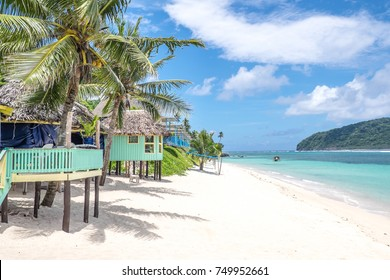 View along Lalomanu Beach, Upolu Island, Samoa, South Pacific, of colorful Samoan beach fale huts that are an alternative to hotel or resort accommodation
