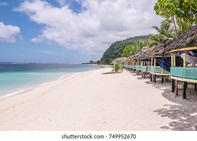 View along Lalomanu Beach, Upolu Island, Samoa, South Pacific, of thatched open-sided Samoan beach fale huts that are an alternative to hotel or resort accommodation