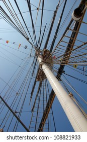 View along a large sail ship's mast into the clear blue sky of London in summer