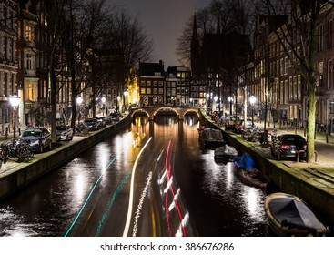 A view along the  Leidsegracht canal in Amsterdam at night. The trail from a boat cna be seen.