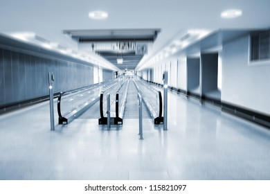 A view along a long moving walkway or moving sidewalk commonly used at modern airport terminals.
