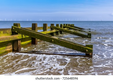 A view along the low side of a groyne on Skegness beach, UK in summer with a wind farm just visible on the horizon