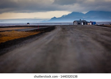View along the only street inside Adventdalen fjord, lonley house next the street, cloudy day in the arctic tundra of Svalbard, Spitsbergen, northern Norway