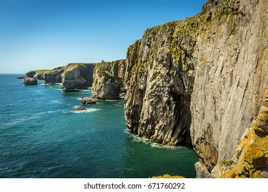 The view along the Pembrokeshire coast, Wales showing the entrance to a Geo (collapsed cave with only entrance remaining), rock stacks and cliff faces in summer
