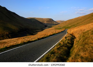 A view along a portion of Mountain road, heading deeper into the Elan Valley in Mid-Wales, coming from Aberystwyth direction. Taken Easter Sunday, 2019, with the sun setting behind.