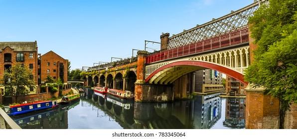 Blick auf einen Eisenbahnviadukt im restaurierten viktorianischen Kanalsystem in Castlefield, Manchester, Vereinigtes Königreich