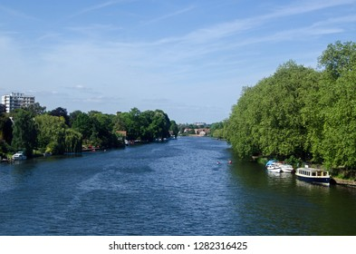 View along the River Thames from Kingston Railway Bridge looking towards Richmond Upon Thames and the landmark Star and Garter Home.  Sunny afternoon in late spring.