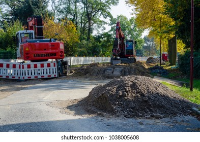 View along a road to diggers at a jobsite in a housing area - Dahlewitz, Germany - 10/15/2017