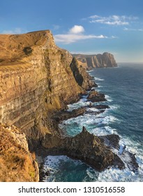 View along the southern coastline of the cliffs and crashing waves on the island of Suduroy in the Faroe Islands.