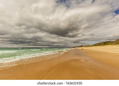 view along a sunny warm beach with heavy clouds above and golden sand and aquamarine blue ocean