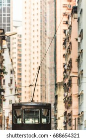 View along tall houses at street in Hong Kong and upper deck of tramway with pantograph and catenary wire/Ride Through Tall Narrow Street