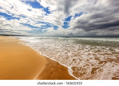 view along a warm sunny sandy beach coastline with waves and water washing ashore and grey clouds overhead