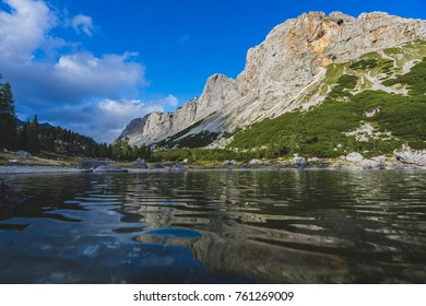 View of a alpine lake. Emerald color of a mountain lake surrounded by high alpine peaks and rock faces. Green forrest in the background. Valley of Triglav Lakes, Triglav National Park, Slovenia.