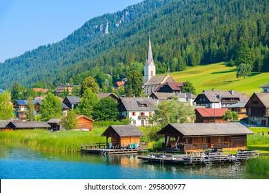 View of alpine village on shore of Weissensee lake in summer landscape Alps mountains, Austria