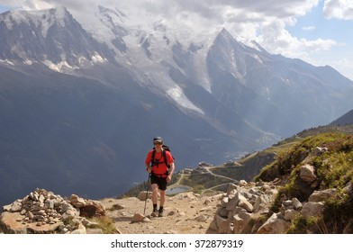 View of Alps mountains and a tourist hiking on a footpath.