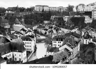 a view of Alzette River passing through the Grund Quarter of Luxembourg City, Luxembourg, with its typical houses with black slate roofs, in black and white