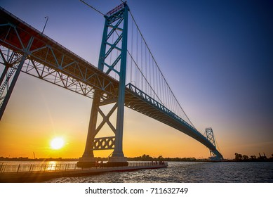 View of Ambassador Bridge connecting Windsor, Ontario to Detroit Michigan at sunset time