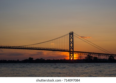 View of Ambassador Bridge connecting Windsor, Ontario to Detroit Michigan at sunset time