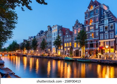 View of the Amsterdam canals and embankments along them at night.