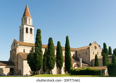 View of the ancient Basilica di Santa Maria Assunta in Aquileia against a blue sky