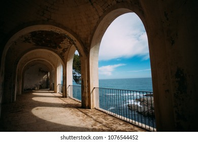 View from ancient building on ocean or sea with roman columns and historic ruins on mediterranean coast line. Beautiful blue sky and waves crush on cliffs. Travel destination for bloggers