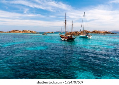 A view of an ancient and a modern sailboat moored in a wonderful and colorful bay of the Mediterranean sea with some rocks in the background on a sunny day with some clouds in summer,in Sardinia Italy