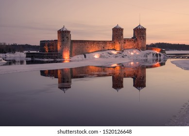 View of the ancient Olavinlinna fortress in March lilac twilight. Savonlinna, Finland