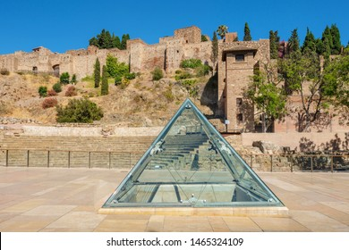 View to ancient Roman amphitheater ruins with Alcazaba fortress in background. Malaga, Andalusia, Spain