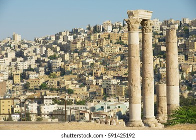View to the ancient stone columns at the Citadel of Amman with the Amman city at the background in Amman, Jordan.