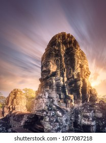 View of ancient temple Bayon Angkor Wat complex with stone faces of buddha and sun rays of sunrise Siem Reap, Cambodia