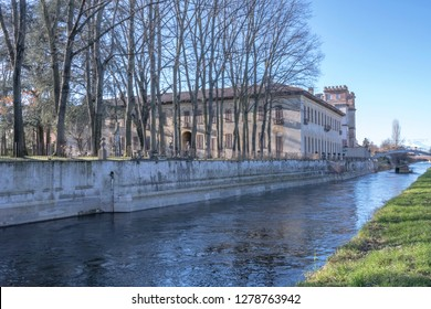 view of ancient Villa and its patk with huge trees on embankment of artificial historic canal, shot in winter bright light at Robecco sul Naviglio, Milan, Lombardy, Italy