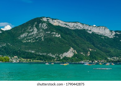 View of Annecy lake,boats with tourists and Alps mountains on sunny day with blue sky in Annecy city.Annecy is the largest city of Haute-Savoie department in France.