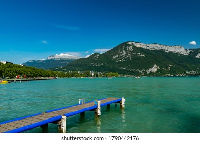 View of Annecy lake,wooden pier,boats with tourists and Alps mountains on sunny day with blue sky in Annecy city.Annecy is the largest city of Haute-Savoie department in France.