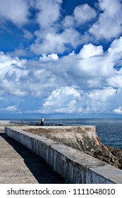 View of anonymous man standing alone on paved seafront of Baracoa city with tranquil water under white clouds, Cuba