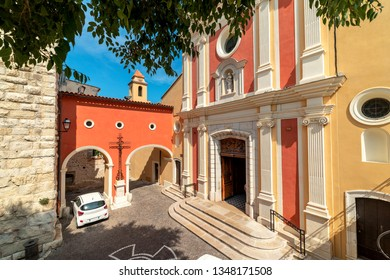 View of Antibes Cathedral on small town square and arched passage in Antibes, France.