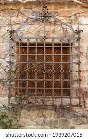 View of antique wrought iron window on a stone facade. Spanish Traditional ornaments.