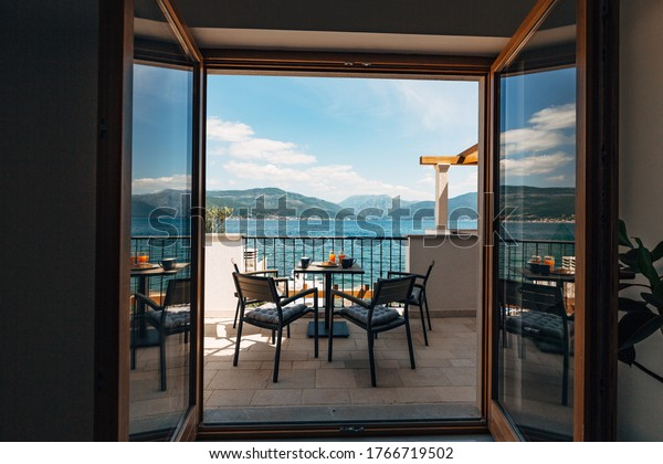 View from the apartment at sea. Balcony with garden furniture and breakfast on the table. Croissants and freshly squeezed orange juice.
