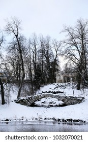 View of the Apollo Colonnade, abandoned stone bridge and Slavyanka river in winter. Pavlovsk, St. Petersburg, Russia