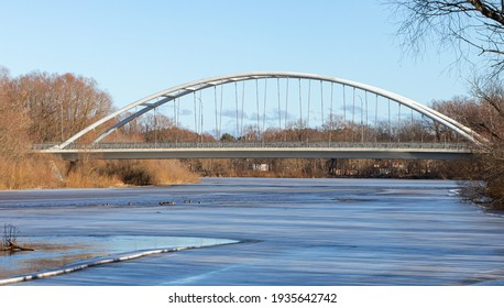 View of the arched bridge over the river on a sunny spring day. Ice is melting in the river. Latvia. Gauja. Bridge over the Gauja