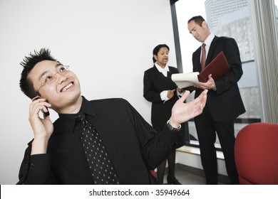 View of architect talking on mobile phone with businesswoman and manager discussing in background.