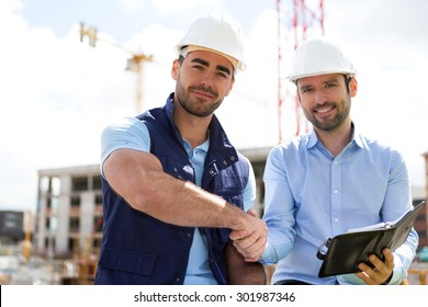 View of an architect and worker handshaking on construction site