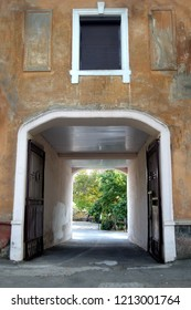a view of an archway with partio behind in old provincial town street