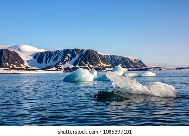 A view of the Arctic island from the sea, beyond the ocean, you can see the shore, the mountains covered with snow and on the water surface small icebergs, the Arctic, the Barents Sea.