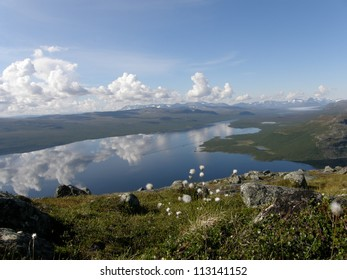 View of arctic Kilpisjarvi lake from the sacred Saana mountain, Lapland, Finland (at the border with Norway); rocks and cotton grass on the foreground